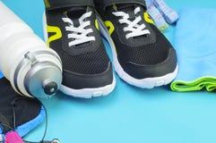 Folâtrez la bouteille, la serviette et les chaussures de course sur le tapis de sport Photo stock
