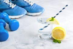 Folâtrez la composition avec de l'eau en verre article de sport avec le citron m Photographie stock libre de droits