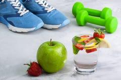 Folâtrez la composition avec le strawb en verre de pomme de l'eau d'article de sport Images stock