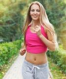 Folâtrez la femme courante de forme physique pulsant pendant la séance d'entraînement extérieure image stock