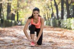 Folâtrez la femme de coureur attachant ses dentelles d'espadrille de chaussure que le sourire heureux préparent pour la séance d' Photos libres de droits