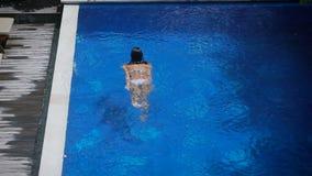 Folâtrez la fille dans un maillot de bain blanc et des flotteurs de lunettes de soleil le long de la piscine dans une station de  banque de vidéos