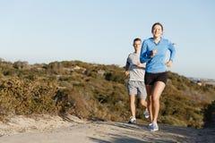 Folâtrez le coureur pulsant sur la plage établissant avec son associé Images stock