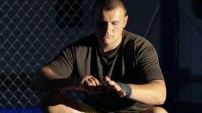 Folâtrez le maître enveloppant des bandages sur sa main avant combat dans le gymnase lentement banque de vidéos