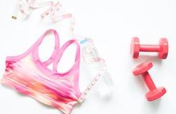Folâtrez le soutien-gorge, la mesurer-bande et les haltères rouges sur le fond blanc Photos stock