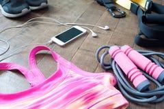 Folâtrez les accessoires de forme physique dans la couleur rose et noire sur le plancher en bois Photographie stock