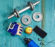 Folâtrez les articles bouteille, les haltères, gants sur le plancher de sport Photographie stock