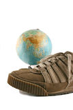 Folâtrez les chaussures à côté d'un globe Photos libres de droits