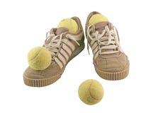Folâtrez les chaussures à côté de 4 billes de tennis Image stock