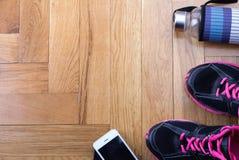 Folâtrez les chaussures avec la bouteille et le téléphone sur le plancher Photo stock