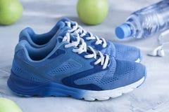 Folâtrez les chaussures, bouteille de l'eau, pommes sur le backround concret gris Images libres de droits