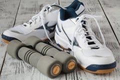 folâtrez les chaussures et les haltères sur le plancher, vue supérieure Backgrou de sport Photographie stock