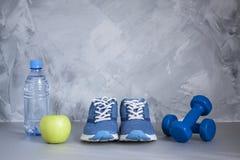 Folâtrez les chaussures, haltères, la pomme, bouteille de l'eau sur le béton gris Photographie stock