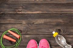 Folâtrez les chaussures, la corde à sauter et la bouteille d'eau sur le fond en bois photographie stock libre de droits