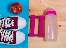 Folâtrez les chaussures, la pomme, la bouteille de l'eau et les haltères Photo stock