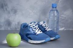 Folâtrez les chaussures, la pomme, bouteille de l'eau sur le backround concret gris Image stock