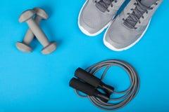 Folâtrez les chaussures, les haltères et la corde à sauter sur le fond bleu Vue supérieure Forme physique, sport et concept sain  Photographie stock libre de droits