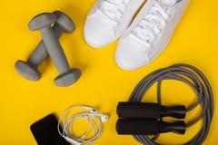 Folâtrez les chaussures, les haltères, le téléphone portable et la corde à sauter sur le fond jaune Vue supérieure Forme physique Photos libres de droits