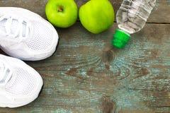 Folâtrez les chaussures, les pommes, bouteille de l'eau sur le fond en bois Concentré Photos stock