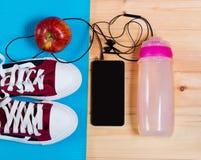 Folâtrez les chaussures sur le tapis de yoga, la bouteille de l'eau, la pomme et le smartphone Photos libres de droits