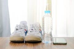 Folâtrez les chaussures une bouteille de l'eau et du téléphone intelligent sur le plancher en bois, s Images stock
