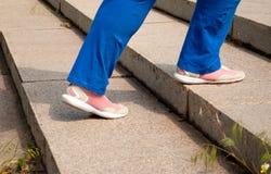 Folâtrez les pieds femelles d'athlète dans des pantalons de sports de bleu et des espadrilles roses Image libre de droits