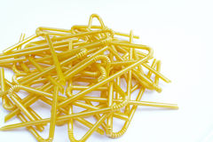 Fold-able joint of yellow milk plastic straw (Selective focus) w. Ith milk plastic straws pile on white ground Stock Image