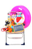 Foldable beach chair full of beach items on a white background. A foldable beach chair full of beach items, such as diving masks, pails and shovels, a beach ball Stock Photography