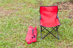 Foldable camping chair with the green lawn background. Royalty Free Stock Images