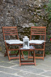 Foldable wooden chairs, mini table with candle lantern on top. Placing outdoor by stone wall Stock Images