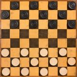 Foldable Wooden Checkerboard. Old scratched foldable wooden checkerboard with wooden pieces in the starting position Royalty Free Stock Photos