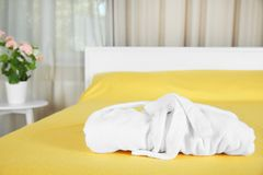 Folded bathrobe on bed. In room royalty free stock photo