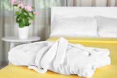 Folded bathrobe on bed. In room stock image