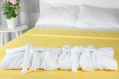 Folded bathrobes on bed stock photography