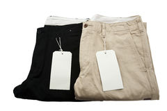 Folded Black and Khaki Trousers with tagging. Isolated stock photo