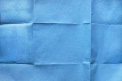Folded blue paper. Folded blank blue wrapper paper as a background royalty free stock photography