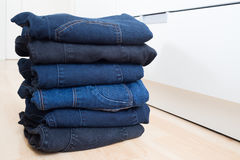 Folded blue and black jeans stacked on wood floor Stock Images