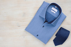 Folded blue man shirt and tie on wooden background stock photos