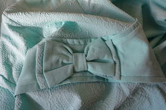 Folded bluish green fabric with bow and ribbon. Folded pastel bluish green fabric with bow and ribbon Royalty Free Stock Images