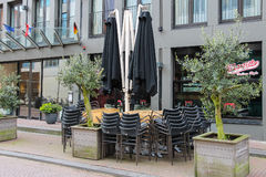 Folded cafe tables and chairs and closed sun umbrellas Royalty Free Stock Images