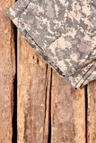 Folded camouflage pattern pants on wooden floor. Cropped image, flat lay, top view Royalty Free Stock Images