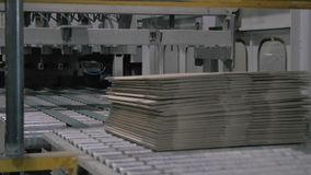 Folded cardboard boxes on modern conveyor belt at factory stock video