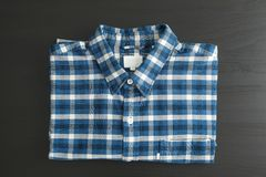 Folded checkered shirt on black table stock photos