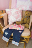 Folded Childrens Clothes. On a Chair Stock Image