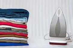 Folded clothing with iron on stripy background. Stock Photo