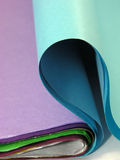 Folded Colored Paper. Closeup view of one end of a stack of colored paper, sometimes called construction paper, folded in different directions Stock Photos