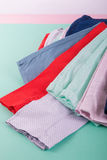 Folded colorful pants and jeans on mint background. Top view Stock Image
