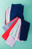 Folded colorful pants and jeans on mint background. Top view. Royalty Free Stock Images