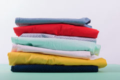 Folded colorful pants and jeans. Stack of bright female trousers. Close up. Royalty Free Stock Images