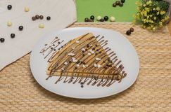 Folded crepe, Russian blini with chocolate sauce on white plate, chocolate chips on topping and dragees on the table. Folded crepe, Russian blini with chocolate stock images